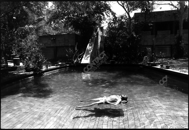 Robert Rauschenberg, artist, relaxing in a pool at a home in Ahmadabad, India, designed by Le Corbusier, 1975