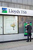 A man withdraws money from an ATM at a branch of Lloyds TSB bank in central London.