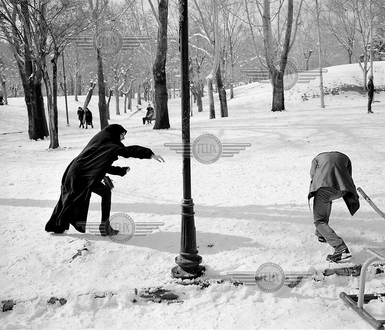 A couple have fun pelting each other with snowballs in a park.