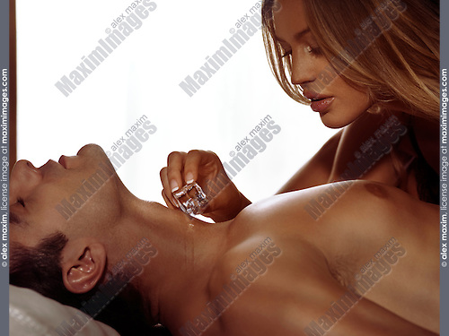 Sensual artistic portrait of sexy couple in bed playing with an ice cube