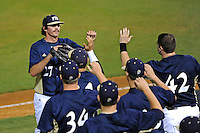 2 March 2012:  FIU pitcher Mason McVay (27) high-fives with teammates at the end of a half-inning as the FIU Golden Panthers defeated the Brown University Bears, 6-5, at University Park Stadium in Miami, Florida.