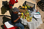 Vendor prepares fruit for sale to tourists during Easter holidays
