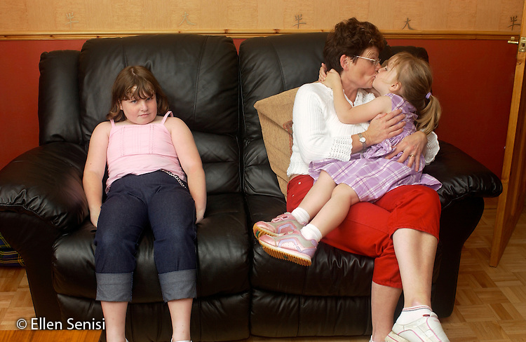 MR / Radley, Abingdon, Oxfordshire, England.Mother and daughters (girls aged 5 and 9) on couch at home. Older sister sits alone while mother holds and kisses youngest child..MR: Web3, Web4, Web2.©Ellen B. Senisi