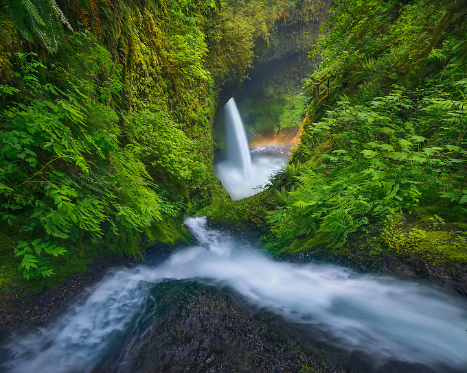 Cascades converge in a steep canyon, leading to a large waterfall below.