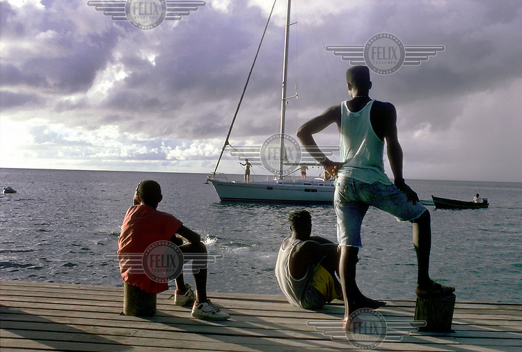 Local youths watch as a tourist yacht sails past the Soufriere seafront.