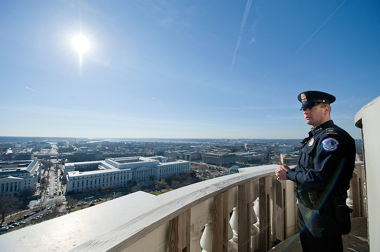 UNITED STATES - Dec 19: U.S. Capitol Policemen Adam Taylor checks out the view to the south from the top of the US Capitol dome during a tour of the dome December 19, 2013 in Washington, DC. The Dome has not undergone a complete restoration since 1959-1960 and due to age and weather is now plagued by more than 1,000 cracks and deficiencies. The Architect of the Capitol began in November, a multi-year project to repair these deficiencies, restoring the Dome to its original, inspiring splendor.  (Photo By Douglas Graham/CQ Roll Call)
