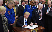 United States President Donald J. Trump, signs an Executive Order to reestablish the National Space Council as Apollo 11 astronaut Buzz Aldrin (R) looks on  in the Roosevelt Room of the White House in Washington, DC, on June 30, 2017. <br /> Credit: Olivier Douliery / Pool via CNP