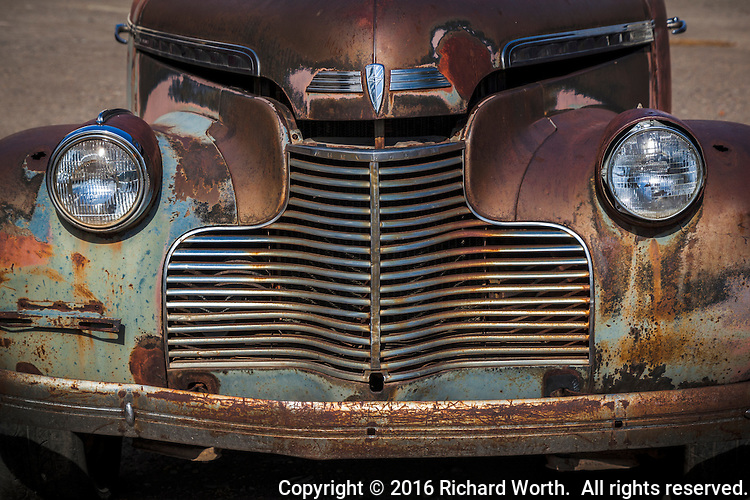 Like a frowing grumpy face, the headlights, and the rusted grill, fenders and front bumper of an ancient Chevy on display along a small town mainstreet, and it's available for sale.