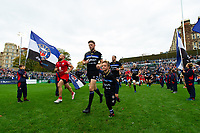 Rhys Priestland, mascot in hand, leads the Bath Rugby team out onto the field. Heineken Champions Cup match, between Bath Rugby and Stade Toulousain on October 13, 2018 at the Recreation Ground in Bath, England. Photo by: Patrick Khachfe / Onside Images
