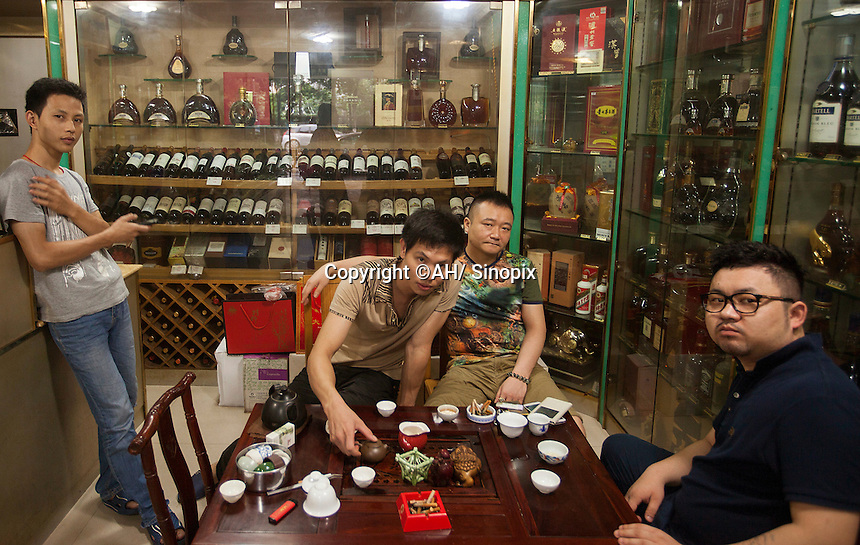 Wine traders are seen in a shop that sells real and fake wine, Guangzhou, Guangdong Province, China, 18 July 2014.<br /> <br /> PHOTO BY SINOPIX