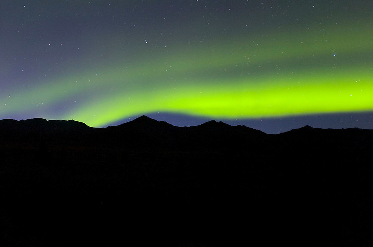 The aurora borealis, or northern lights, rises above mountains in the Alaska Range bordering the Denali Park Road. Road permit lottery winners have until midnight to finish their drive on the normally closed portion of road, leaving plenty of opportunity to look for the special sight.