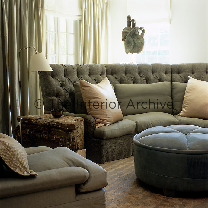 A giant carved hand is silhouetted against the window in a bedroom where the contrasting textures of a rough stone side table, linen sofa, velvet pouffe and waffle-cotton cushions are unified in toning shades of soft grey