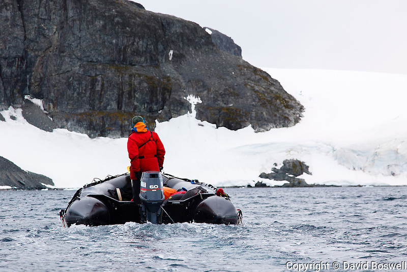 A zodiac provides safety for a group of sea kayakers near Cuverville Island just off the Antarctic Peninsula.