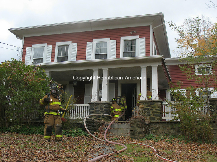 ROXBURY, CT - 22 October 2010 - 102210RH02 - Firefighters work to douse and ventilate a smouldering fire at 339 Painter Hill Road in Roxbury. Nobody was home at the time. Rick Harrison Republican-American