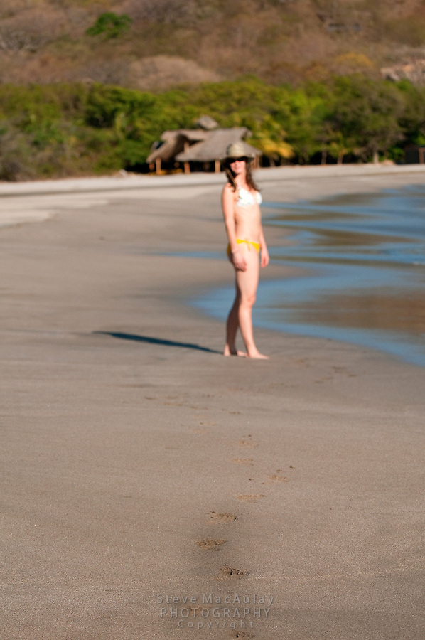 Footprints in the sand on the beach, Young woman in yellow bikini walking and playing on private beach at Morgan's Rock Hacienda and Eco Lodge, Nicaragua