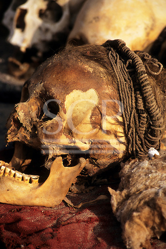 Near Nasca, Peru. Skull with braided hair and skin, showing teeth badly worn down; Chauchilla cemetary.