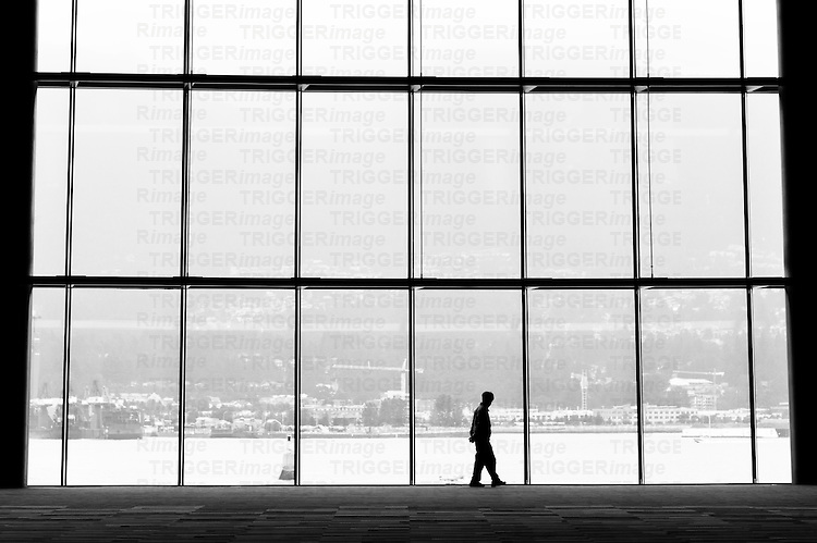 Silhouetted man with hands behind his back walking across large window with city in background.