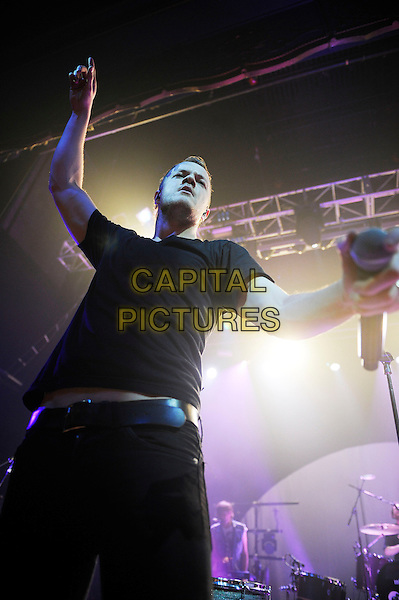 Dan Reynolds of Imagine Dragons.Imagine Dragons performing in concert, The Forum, London, England, UK, 11th April 2013..music live on stage gig half length black t-shirt microphone jeans arm raised up .CAP/MAR.© Martin Harris/Capital Pictures.