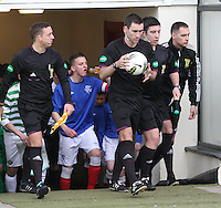 Match referee Steven Brown flanked by his assistants Steven Streng and David Burns lead out the teams in the Celtic v Rangers City of Glasgow Cup Final match played at Firhill Stadium, Glasgow on 29.4.13,  organised by the Glasgow Football Association and sponsored by City Refrigeration Holdings Ltd.