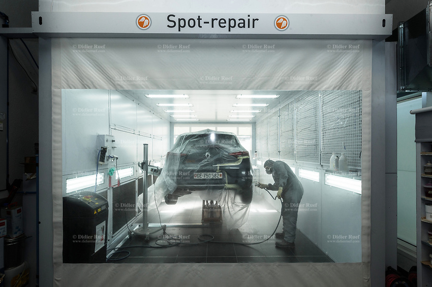 "Switzerland. Canton Geneva. Plan-les-Ouates. Renault Retail Group, RRG Suisse. ""Spot-repair"" by Dells Angels. Renault Clio car inside a paint booth in auto body repair garage. After filling bumpy part and grinding automobile car body in garage workshop, the mechanic worker is painting the repaired spot. 4.03.2020 © 2020 Didier Ruef"