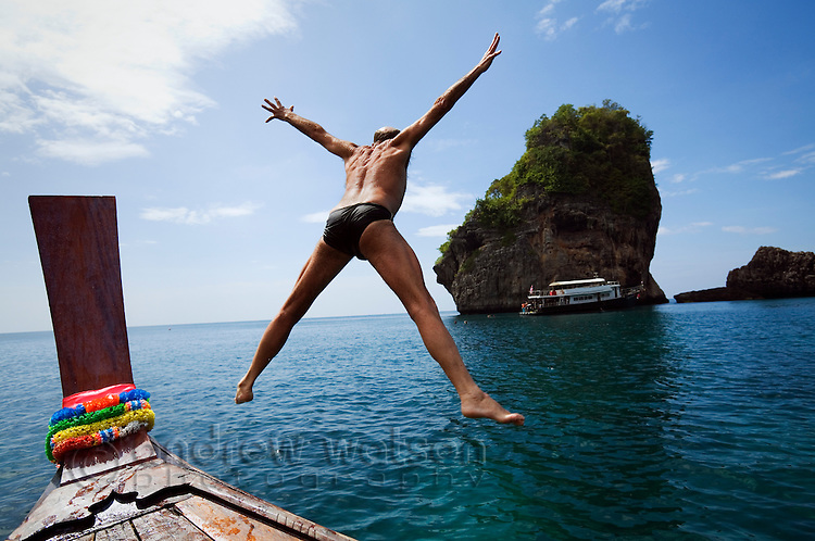 A tourist leaps from a longtail boat into the waters of the Andaman Sea.  Phuket, Phuket province, THAILAND.