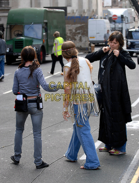 "SIENNA MILLER.On the set of her new film ""Hippie Hippie Shake"", outside The Old Bailey, London, England, September 16th 2007..full length film set filmset jeans  hairband head band cream fringed tassled waistcoat costume seventies style back behind ponytail scrunchie.CAP/IA.©Ian Allis/Capital Pictures"