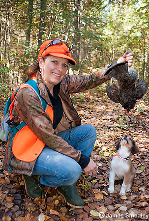 Hunter holding up a ruffed grouse to their family pet dog.