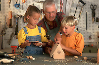 Grandfather helps two children with birdhouse project.<br />