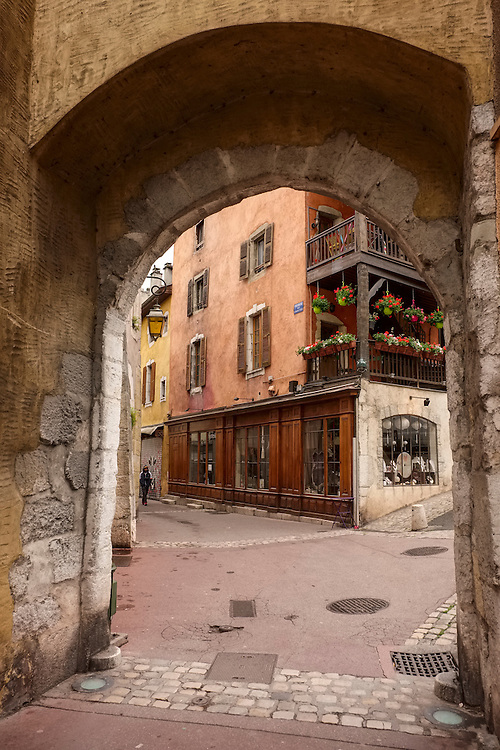 Narrow pedestrian streets emerge from quaint buildings in the city of Annecy, French Alps.