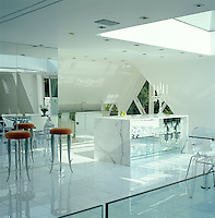 The living area of the penthouse has a white Carrara marble floor which has also been used for the free-standing island in the kitchen