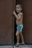 boy with painted tattoo flirts with camara in Havana Veija, Cuba