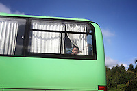 A young boy peers out of the back of a public bus in Zhanjiang, Guangdong Province. 2010