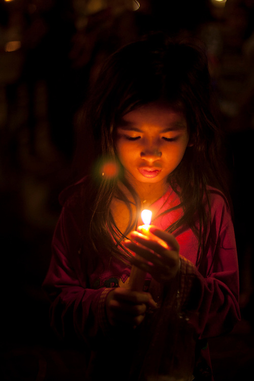 A young Cambodian girl prays at a small shrine next to the Mekong River in Phnom Penh, Cambodia. <br /> <br /> Photos &copy; Dennis Drenner 2013.