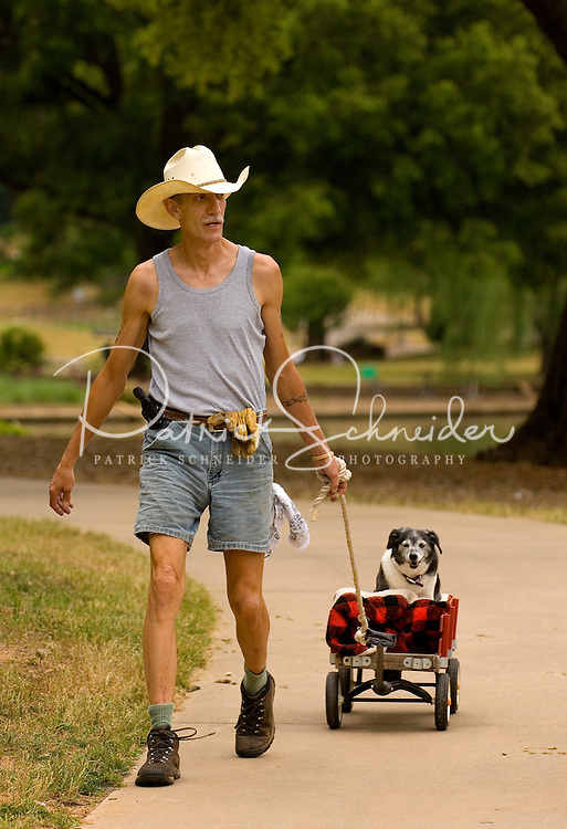A man in a cowboy hat pulls his dog in a wagon at Freedom Park in the Myers Park neighborhood in Charlotte, NC. Myers Park is one of the premier neighborhoods in North America and known for its large canopy of trees.