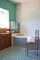 In the Moroccan-inspired bathroom the floor and bath surround are lined in vivid green tiles