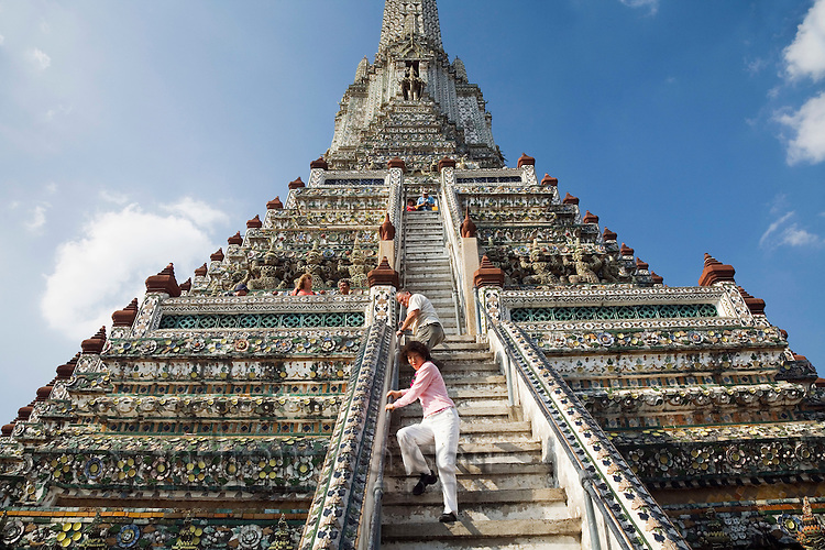 Tourists scale the steps of the 82 metre high Khmer-style prang of Wat Arun.  Bangkok, THAILAND.