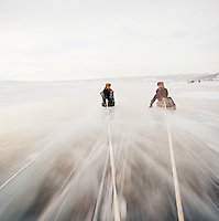 Men sat on tyres being pulled by a car on the frozen Lake Biakal, Irkutsk, Siberia, Russia