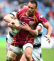 PICTURE BY VAUGHN RIDLEY/SWPIX.COM - Rugby League - Super League - Huddersfield Giants v Hull FC - Galpharm Stadium, Huddersfield, England - 09/04/12 - Huddersfield's Jason Chan is tackled by Hull FC's Jamie Ellis.