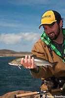 Man holding the Arctic char he caught fly fishing in the Arctic ocean near Nunavut, Canada.