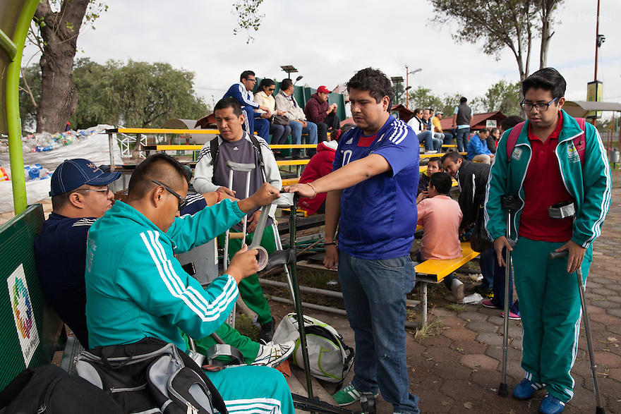 """Players from Guerreros Aztecas reinforce their crutches with gaffer-tape ahead of a soccer game against Los Dragones (""""the Dragons"""")  in Deportivo Tlalli II in Talnepantla, Mexico on September 27, 2014. Guerreros Aztecas (""""Aztec Warriors"""") is Mexico City's first amputee football team. Founded in July 2013 by five volunteers, they now have 23 players, seven of them have made the national team's shortlist to represent Mexico at this year's Amputee Soccer World Cup in Sinaloathis December.The team trains twice a week for weekend games with other teams. No prostheses are used, so field players missing a lower extremity can only play using crutches. Those missing an upper extremity play as goalkeepers. The teams play six per side with unlimited substitutions. Each half lasts 25 minutes. The causes of the amputations range from accidents to medical interventions – none of which have stopped the Guerreros Aztecas from continuing to play. The players' age, backgrounds and professions cover the full sweep of Mexican society, and they are united by the will to keep their heads held high in a country where discrimination against the disabled remains widespread.(Photo byBénédicte Desrus)"""