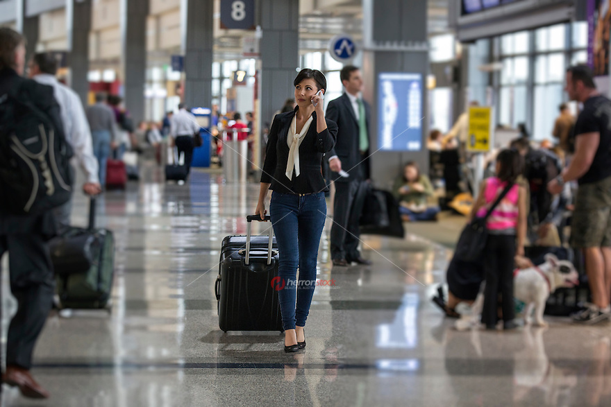 Pretty young female businesswoman holds conversation on cell phone and carries luggage at the Austin–Bergstrom International Airport (ABIA).