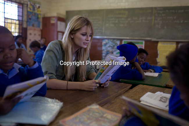 SOWETO, SOUTH AFRICA - SEPTEMBER 1: Mischa Barton, the actress and model, visits a class at Winnie Ngwevekazi Primary School on September 1, 2008 in Soweto, outside Johannesburg, South Africa. Mischa Barton spent 2 days visiting Save The Children supported projects in South Africa, meeting school children and young children. Save The Children are helping about 51,000 children made by HIV/AIDS and poverty to access food, healthcare, social security and education. (Photo by Per-Anders Pettersson/Getty Images For Save The Children).
