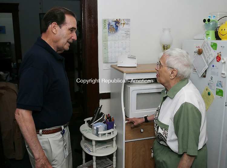WATERBURY, CT 07/11/08- 071108BZ01-  Walter Biscardi, Lifeline installer for VNA Health Care Inc., talks with Helen Gaylord in her Waterbury home Friday morning.  Biscadi, who is 75-years-old and still working, was there to do a test of her system.   <br />  Jamison C. Bazinet Republican-American