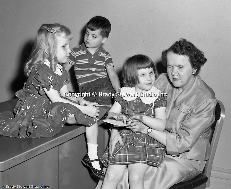 Pittsburgh PA: Assignment for prominent Pittsburgh Attorney C.K. Robinson to promote the Western Pennsylvania School for the Blind - 1955.  The photos were used in a brochure to create awareness and raise money for the School for the Blind. View includes Mrs. Davis practicing reading braille with the children.