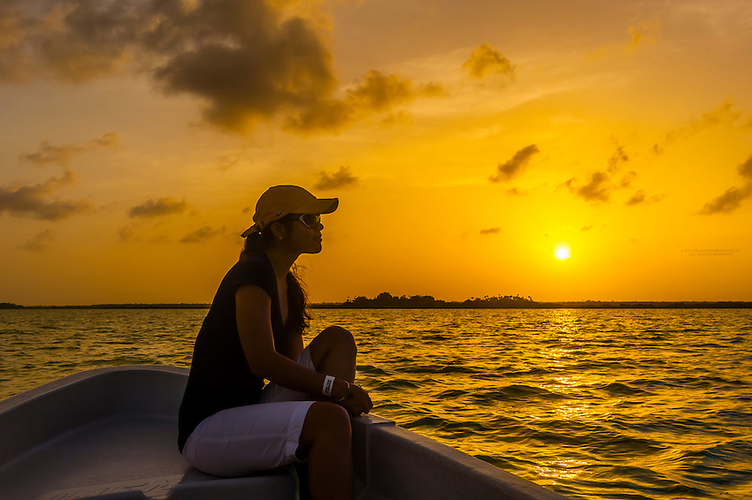Woman in a ponga boat crossing the Sian Ka'an Biosphere Reserve at sunset, which is a small ecotourism and education center, it serves as a model for sustainable development in sensitive tropical ecosystems. It is a UNICEF World Heritage Site and is the third largest natural protected area in Mexico.
