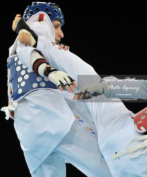 Mohammad Bagheri Motamed (IRI) takes a kick from Claudio Treviso (ITA). London Prepares Taekwondo Invitational International. Excel. London. 03/12/2011. MANDATORY Credit Garry Bowden/Sport in Pictures - NO UNAUTHORISED USE - 07837 394578.