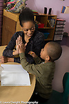 "Education Preschool 3-4 year olds female teacher gives boy a ""high five"" for signing in in the morning"
