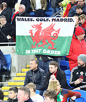 19th November 2019; Cardiff City Stadium, Cardiff, Glamorgan, Wales; European Championships 2020 Qualifiers, Wales versus Hungary; A Wales fan holds a flag that read 'Wales. Golf. Madrid.' joking about recent media around Gareth Bale of Wales - Editorial Use
