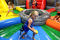 NWA Democrat-Gazette/DAVID GOTTSCHALK Caroline Lieux, 7, retrieves a ball Tuesday, June 25, 2019, during a game of Hippo Chow Down Inflatable at Kanakuk Kamps KampOut! Day Camp at Mount Sequoyah Center in Fayetteville. The camp offers five days of faith-based, day camp activities to children ages 5 to 12 years old. The activities included a zip line, inflatables as well as worship time and small group time with counselors.