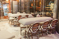"An empty snow covered outdoor cafe in New York during a snow storm on Tuesday evening, January 21, 2014. The official snowfall in Central Park was 11 inches (28 centimeters) which was a record for the day.  Brutal ""Polar Express"" temperatures in the single digits accompanied the snow with the arctic temperatures expected to last several days.  (© Richard B. Levine)"